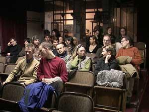 Während das Publikum dem Filmbeginn entgegenfiebert, überlegt der Produzent draußen im Foyer,
